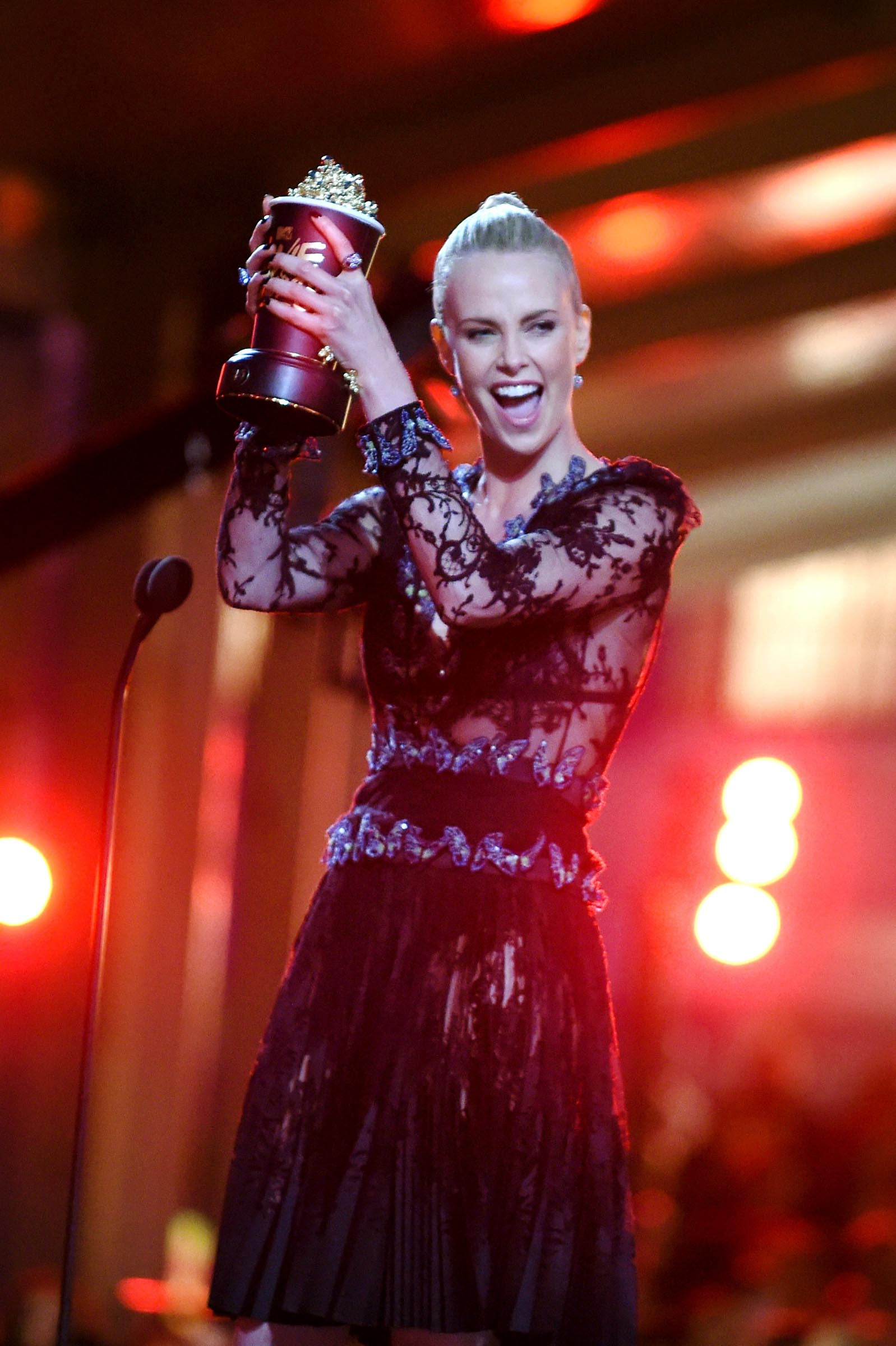 """BURBANK, CALIFORNIA - APRIL 09:  Actress Charlize Theron accepts Best Female Performance for 'Mad Max: Fury Road' onstage during the 2016 MTV Movie Awards at Warner Bros. Studios on April 9, 2016 in Burbank, California.  MTV Movie Awards airs April 10, 2016 at 8pm ET/PT.  (Photo by Emma McIntyre/Getty Images for MTV)"""